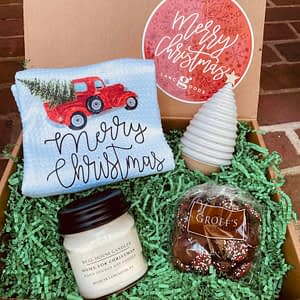 Christmas gift box with chocolate candy, candle, porcelain Christmas tree and Merry Christmas towel.